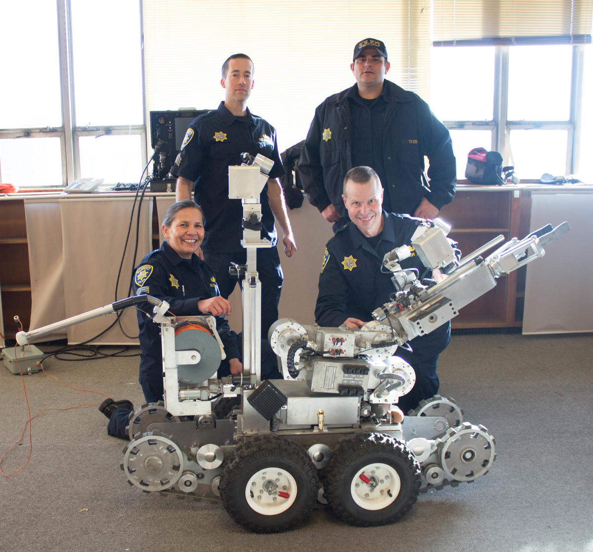 Four bomb squad officers around explosive ordnance robot
